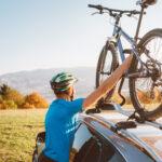 Rowerzysta zdejmujący rower z dachu samochodu