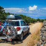 Samochód z boksem dachowym i platformą na rowery jadący na aktywny wypoczynek w Europie